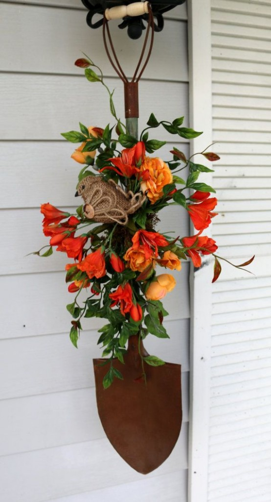 a bright faux bloom decoration with greenery, a burlap bird and a shovel is a nice rustic outdoor decoration