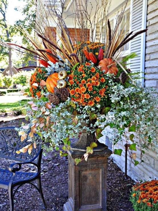 a bold and lush fall arrangement of a vintage urn with faux blooming branches, lotus, dried leaves, twigs, faux pumpkins and lots of other stuff for outdoors