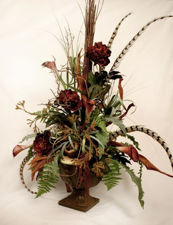 a stylish fall centerpiece of a vintage urn, greenery, feathers and faux blooms is an elegant boho-inspired decoration to make for fall