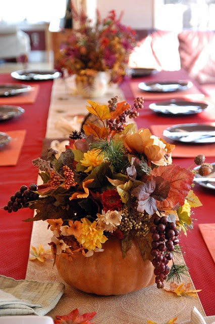 a bright fall centerpiece of a pumpkin, bright fall leaves, berries, fir branches is a stylish decoration you can make yourself