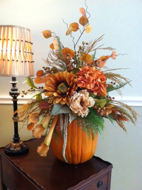a pumpkin with greenery, bright faux blooms, twigs, branches is a stylish fall centerpiece or decoration