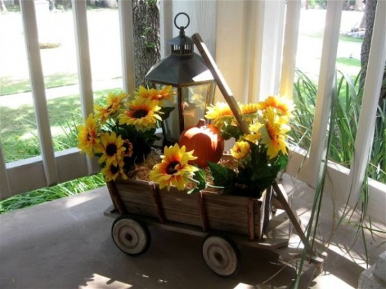 a rustic arrangement of a wooden cart, hay, a faux pumpkin and sunflowers, a candle lantern is a stylish outdoor decoration