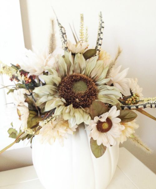 an elegant fall centerpiece of a white pumpkin, faux blooms, foliage and dried touches is a stylish centerpiece idea