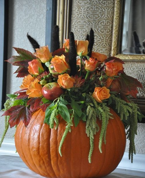 a pumpkin with greenery, faux apples, faux orange blooms and feathers is a stylish fall centerpiece or decoration