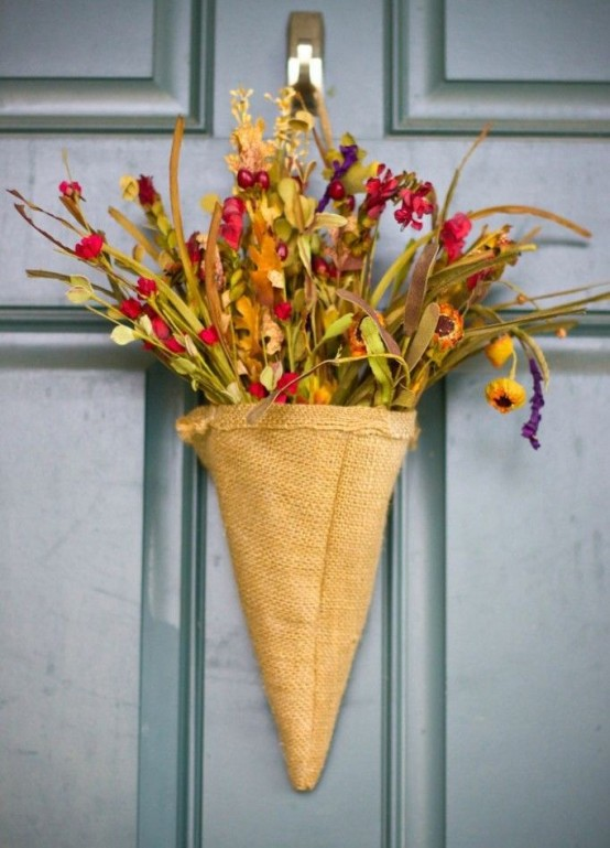 a rustic door arrangement of a burlap cone, faux blooms and greenery is a nice alternative to a usual door wreath