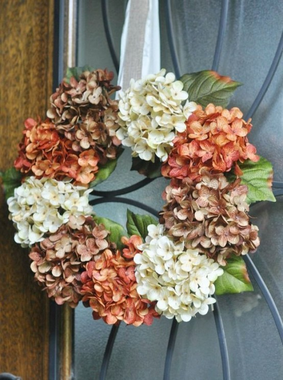 a vintage-inspired faux hydrangea wreath in brown, rust and white on a silk ribbon is a veyr stylish idea for decor