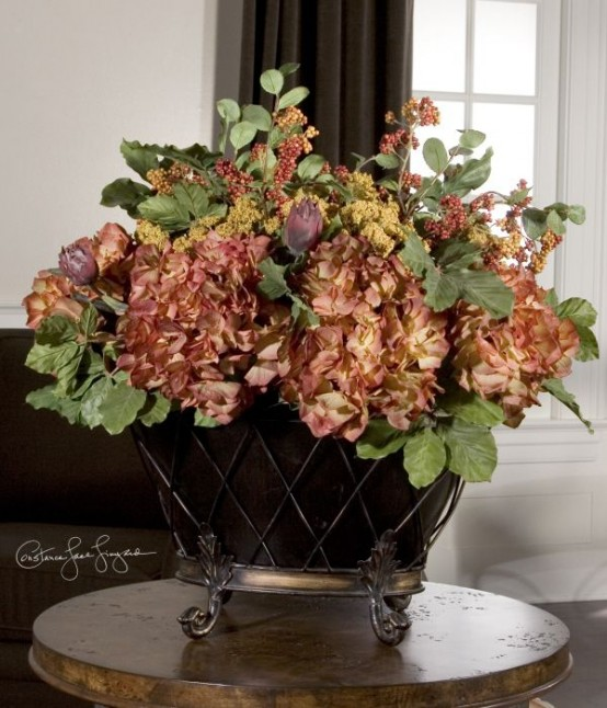 a vintage urn with faux greenery and dried blooms is a refined and chic centerpiece for the fall