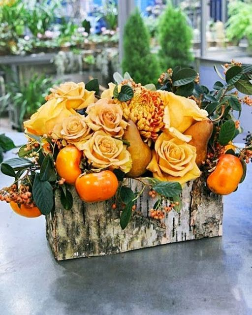 a bright fall centerpiece of a birch bark box with greenery, faux orange roses and fruits is a refined rustic piece