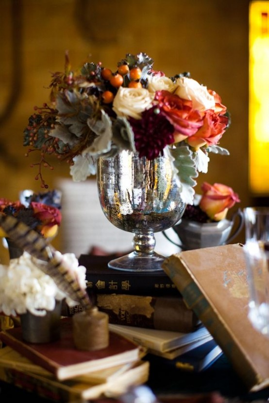 a chic vintage centerpiece of a stack of books, a silver bowl with bright and white blooms, pale greenery and faux and real flowers