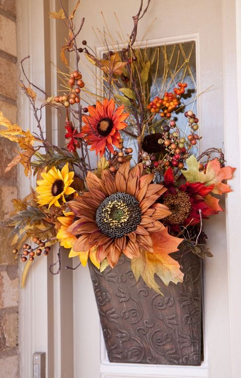 a lovely fall faux flower arrangement with leaves, berries and twigs in traditional fall colors will substitute a usual wreath