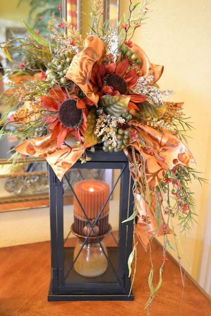 a fall candle lantern with a rust-colored candle, dried grasses, berries and faux blooms and plaid ribbons for the fall