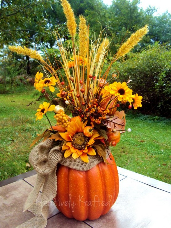 a fall arrangement of a faux pumpkins, a burlap bow, bright faux blooms, berries and branches is a stylish centerpiece