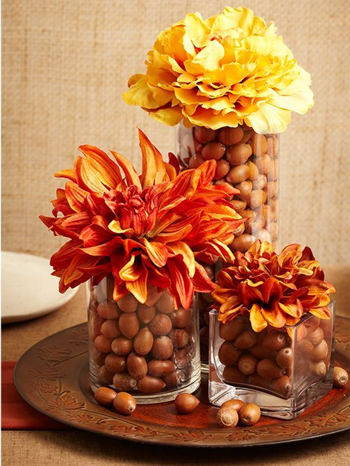 a fall centerpiece of a tray with glasses with nuts topped with large bright fall blooms is a stylish centerpiece to rock