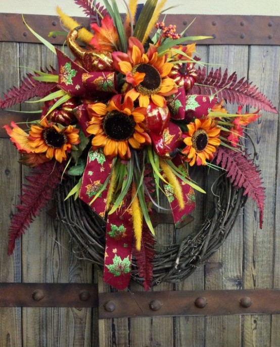 a fall wreath with bright faux blooms, leaves and ribbons is a stylish and long-lasting outdoor decoration with a rustic feel