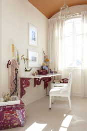 a girlish home office in neutrals, with some boho touches, a floating desk with pink touches, a bright fuchsia ottoman, bold textiles and jewelry