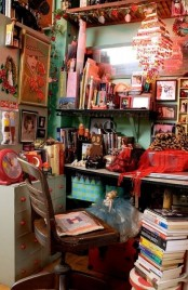 a colorful and fun boho home office in green and red, bold artworks and books, a vintage desk and chair and lots of mess