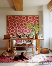 a creative boho chic home office with a wooden desk and stool, a comfy sofa for sitting, a pink wall hanging and a rug plus tropical leaves