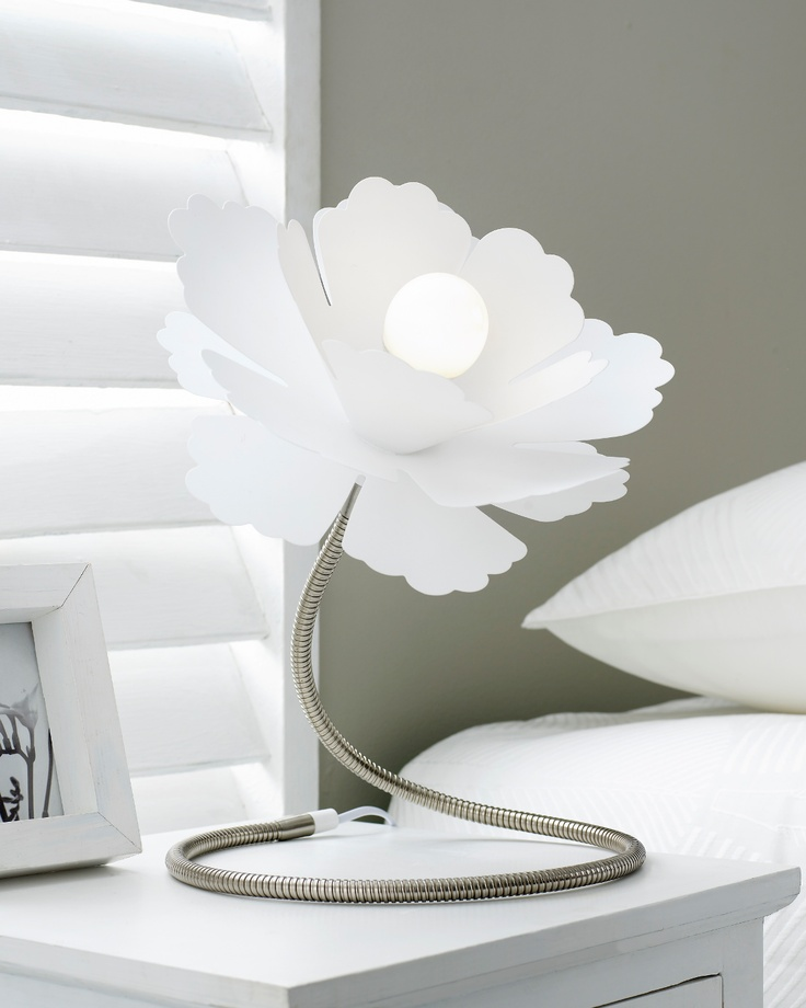 a white flower shaped table lamp of metal with a large lampshade is a creative addition to a bedroom