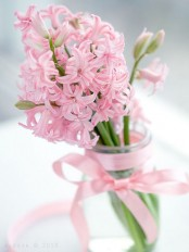a clear vase with a pink ribbon bow and pink bulbs is a lovely and bright spring decor idea for your space