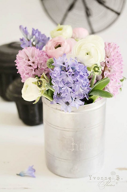 a tin can with pastel and white spring blooms is a beautiful and cool rustic arrangement for your spring-infused space