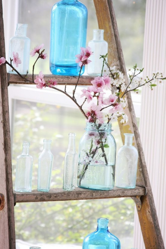 a ladder with vintage bottles and vases and a jar with white and pink cherry blossom for a shabby chic or rustic space