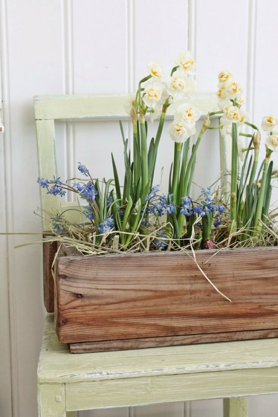 a wooden box with blue and creamy spring blooms and some hay looks very rustic and relaxed and will fit both an indoor and an outdoor space