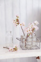 a wire basket with bottles and blush cherry blossom is a lovely rustic and shabby chic arrangement for spring
