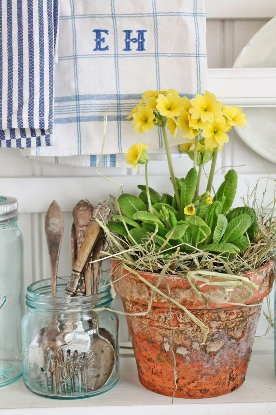 a terracotta planter with bold yellow blooms and hay is a lovely idea for a spring space and will add a rustic feel at the same time