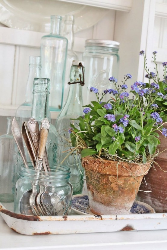 terracotta planters with purple blooms and hay for a slight rustic sprign feel in your space or outdoors, on the porch
