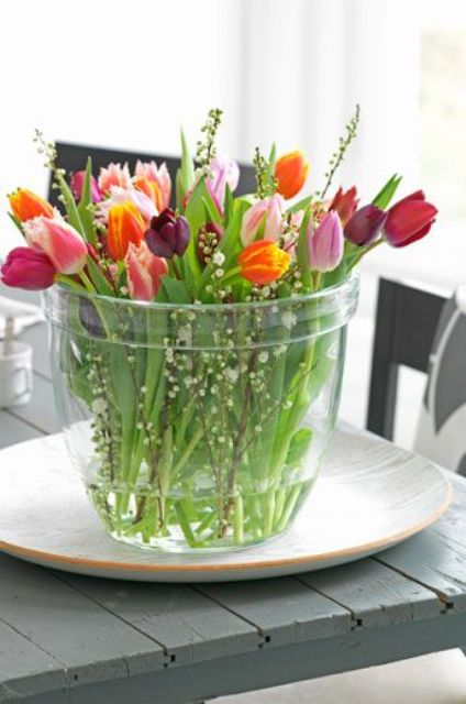 a large jar with colorful tulips and willow is a gorgeous centerpiece for spring with a modern and simple feel
