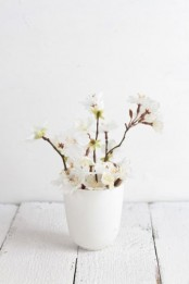 a white vase with white cherry blossom is a lovely and fresh idea that will bring a spring feel and a cool aroma to the space