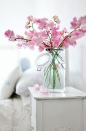 a clear vase with pink cherry blossom is a beautiful idea for adding a spring touch to the space and some color, too