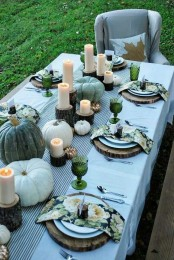 a grey and green Thanksgiving tablescape with heirloom pumpkins, candles, green printed napkins and green glasses, wood slices and tree stumps