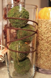 a tall vase with moss balls and twine wrapping it is an east fall or Thanksgiving decoration to rock