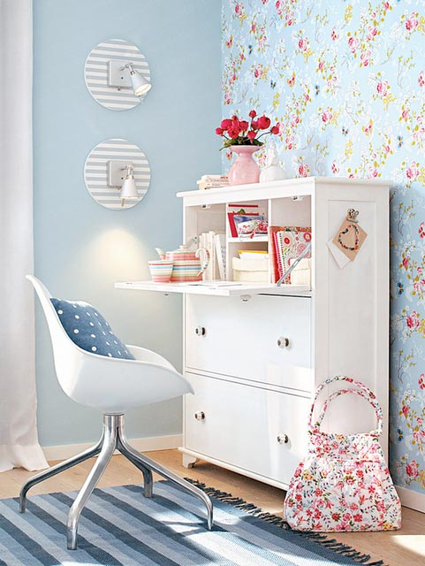 a blue and red floral print wall, some fresh blooms and a blue printed pillow for a fresh spring feel in the space
