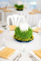 a pretty spring wedding centerpiece of wheatgrass in a bowl, with yellow blooms and a large candle in the center