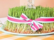 a spring wheatgrass decoration with a glass in the center and a striped ribbon bow is vivacious and cool