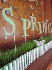 a long turquoise planter with wheatgrass, green letters on skewers and a butterfly is a cool spring decoration to rock
