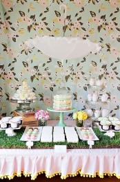 wheatgrass in a tray is used as a backdrop for a dessert table to give it a fresh spring feel