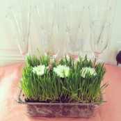 a sheer bowl with wheatgrass and white blooms is a stylish spring decor idea
