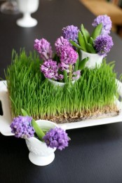 a tray with wheatgrass, with purple and pink blooms in vases is a lovely and vivacious spring centerpiece or decoration