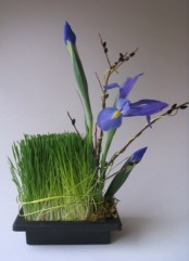 a stone square planter with wheatgrass, purple blooms and willow is a refined centerpiece or decoration