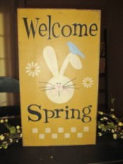 a sunny yellow sign with black letters and a bunny, with a bird and bright blooms is a lovely idea