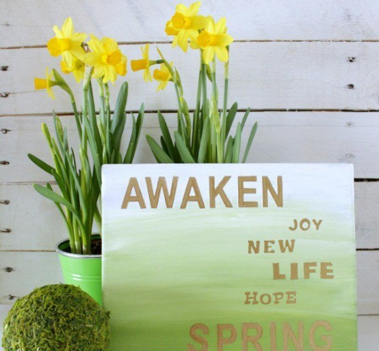 an ombre white to green spring sign with gold letters and blooms in pots is a very lovely spring decoration