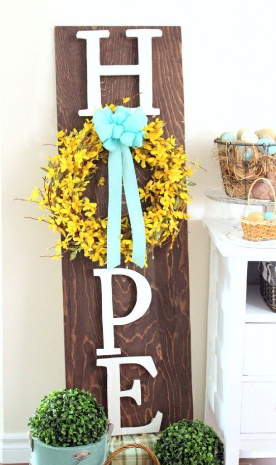 a rustic spring sign with letters, a yellow wreath and a blue bow plus potted greenery for a fresh spring feel