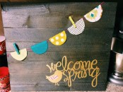 a rustic spring sign with a colorful banner and yellow calligraphy plus a bird is a lovely idea with a touch of fun