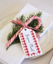 a Christmas place setting done with white porcelain, white linens, a fir twig, a candy cane and a tag is a fun and bold idea