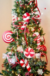 bright Christmas tree decor with red ribbons and oversized red and white fabric peppermints and candy canes looks fun and bold