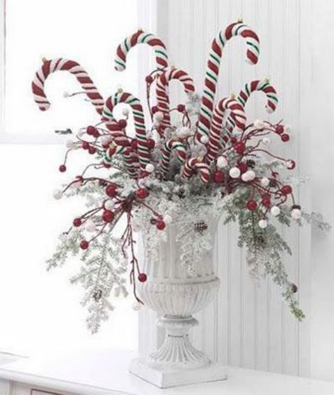 a bold Christmas arrangement in a vintage urn, oversized faux candy canes and snowy and frozen branches is a lovely idea