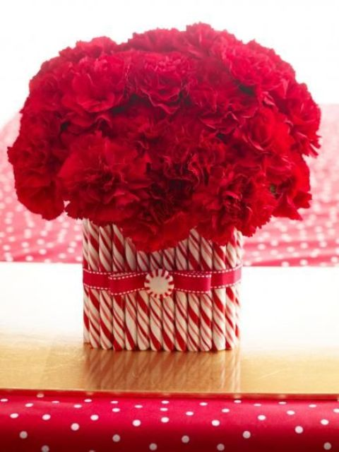 a bright Christmas centerpiece of a vase with red blooms and lots of candy canes covering it is a very chic and lovely idea